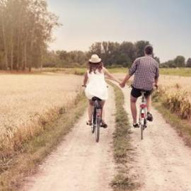 A couple, riding bikes while holding hands