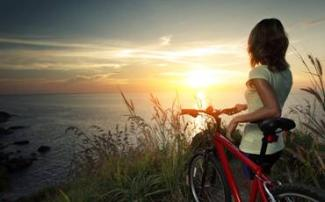 A woman holding a bike, watching the sun set over the sea