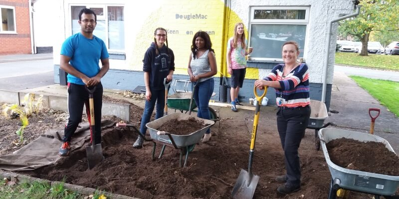 Group of students with shovels and wheelbarrows creating green space