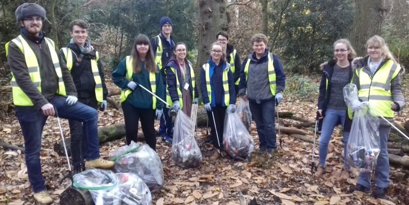 Group of students wearing hi-vis jackets and carrying bags of collected litter